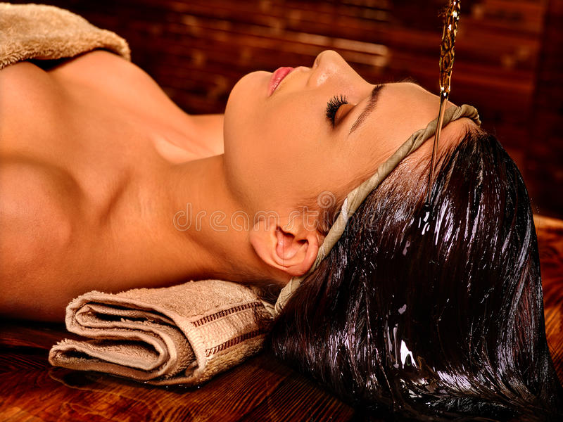 Mujer que tiene aceite de colada de Shirodhara en la cabeza en el balneario de la India imágenes de archivo libres de regalías