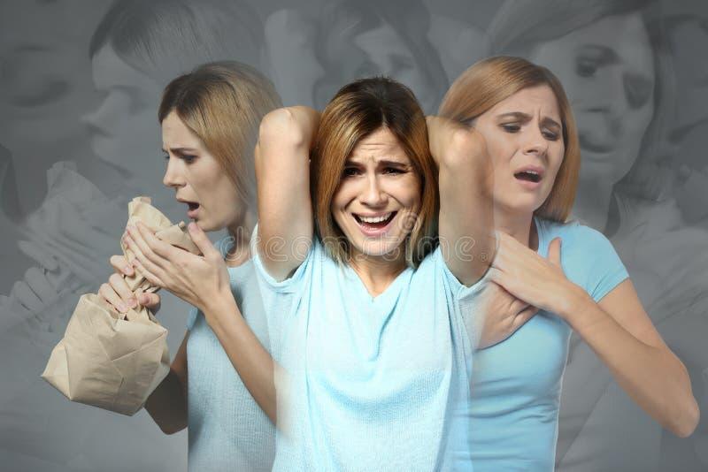Mujer que tiene ataque de pánico en fondo gris imagenes de archivo