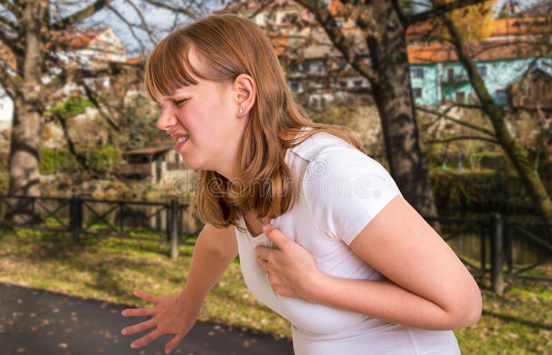 Mujer que tiene ataque del corazón en parque del otoño imagenes de archivo