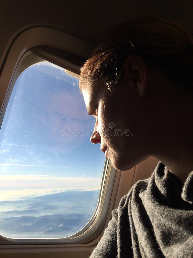 Mujer que tiene cuidado las ventanas de un aeroplano fotos de archivo libres de regalías