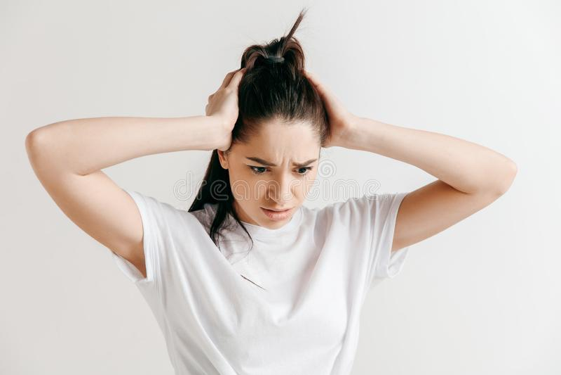Mujer que tiene dolor de cabeza Aislado sobre fondo gris imagenes de archivo