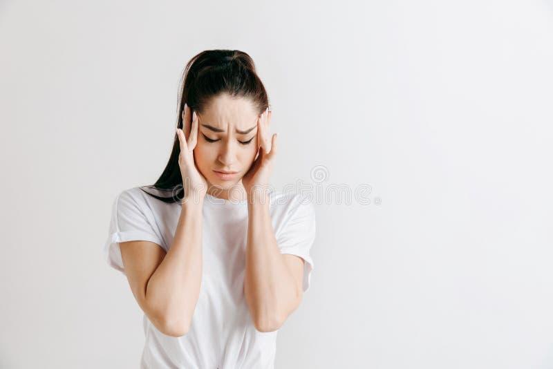 Mujer que tiene dolor de cabeza Sobre fondo gris imagen de archivo libre de regalías