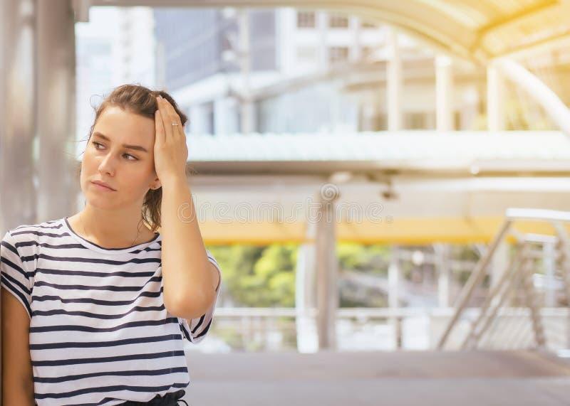 Mujer que tiene manos de un dolor de cabeza que se sostienen en la frente en la calle, el pensamiento femenino y haber importado  foto de archivo