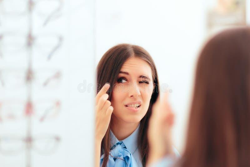 Mujer que tiene problema que pone en las lentes de contacto foto de archivo