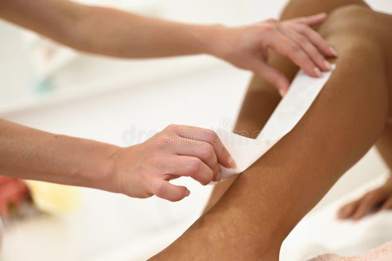 Mujer que tiene procedimiento de retiro del pelo en la pierna que aplica la tira de la cera imágenes de archivo libres de regalías