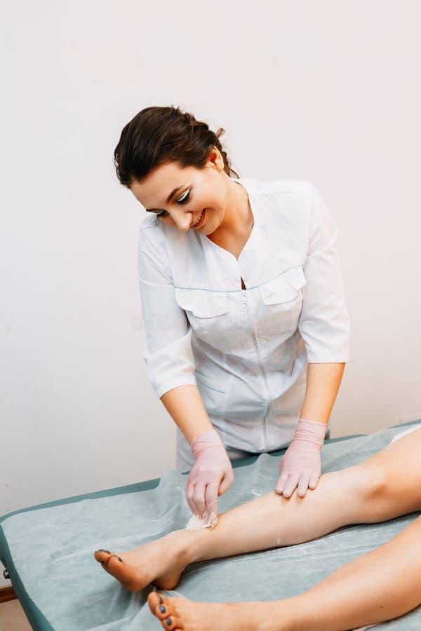 Mujer que tiene procedimiento de retiro del pelo en la pierna con azucarar la goma fotos de archivo