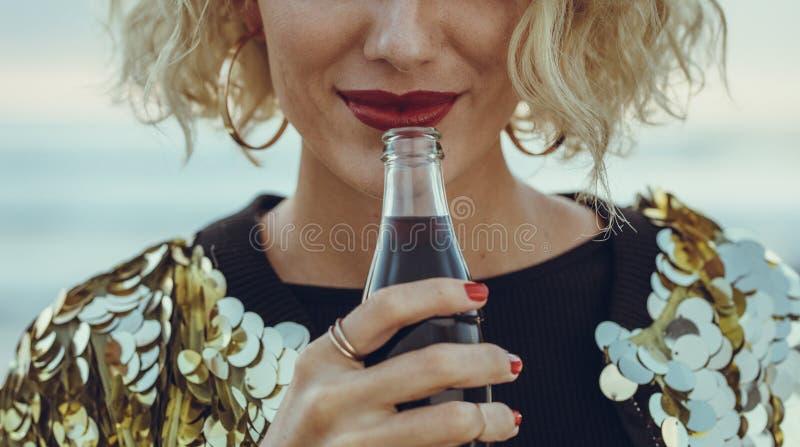 Mujer que tiene refrescos en la playa foto de archivo