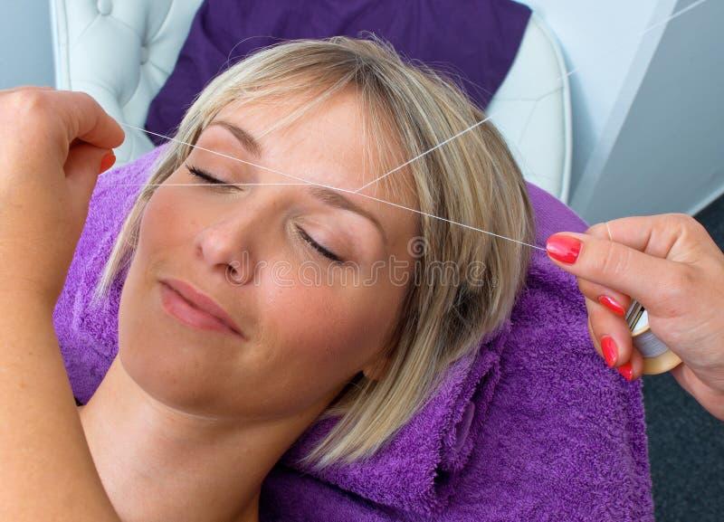 Mujer que tiene roscar procedimiento de retiro del pelo foto de archivo libre de regalías