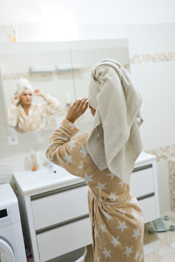 Mujer que tiene toalla blanca en la cabeza despu?s de tomar una ducha imagen de archivo libre de regalías