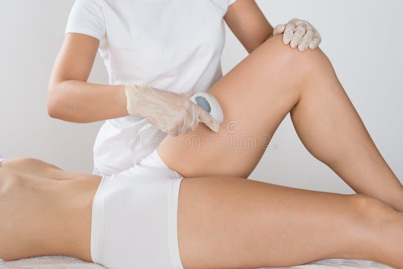 Mujer que tiene tratamiento del laser en muslo fotos de archivo