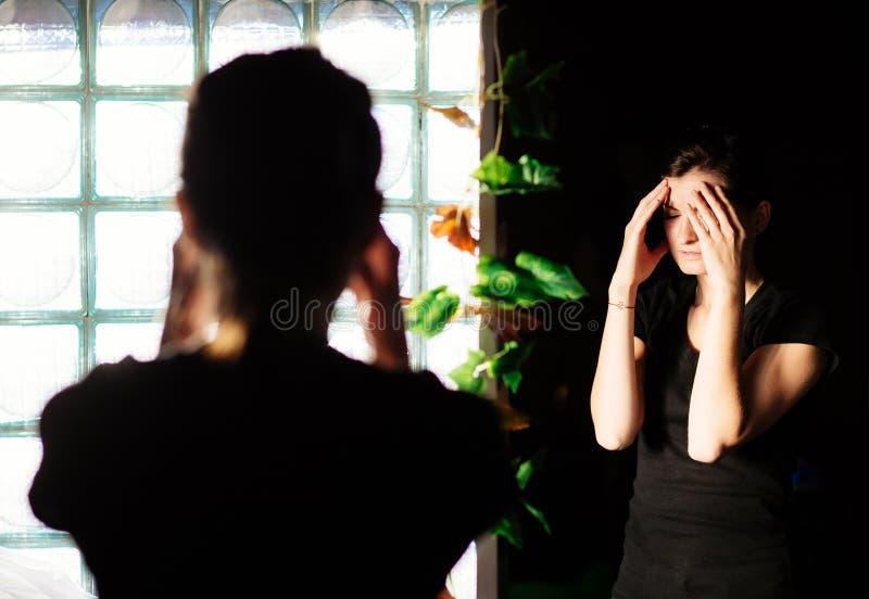 Mujer que tiene un dolor de cabeza delante de un espejo imagenes de archivo