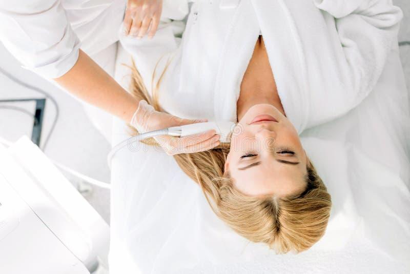 Mujer que tiene un tratamiento facial estimulante de un terapeuta foto de archivo