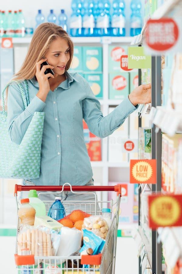 Mujer que tiene una llamada de teléfono en la tienda fotografía de archivo