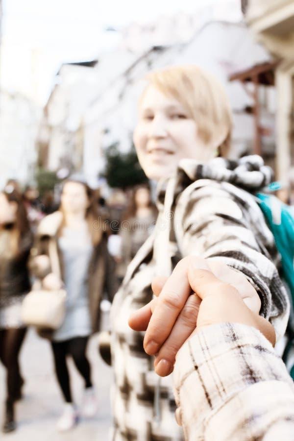 Mujer que tira alguien mano y que camina hacia la calle apretada de la ciudad fotografía de archivo libre de regalías