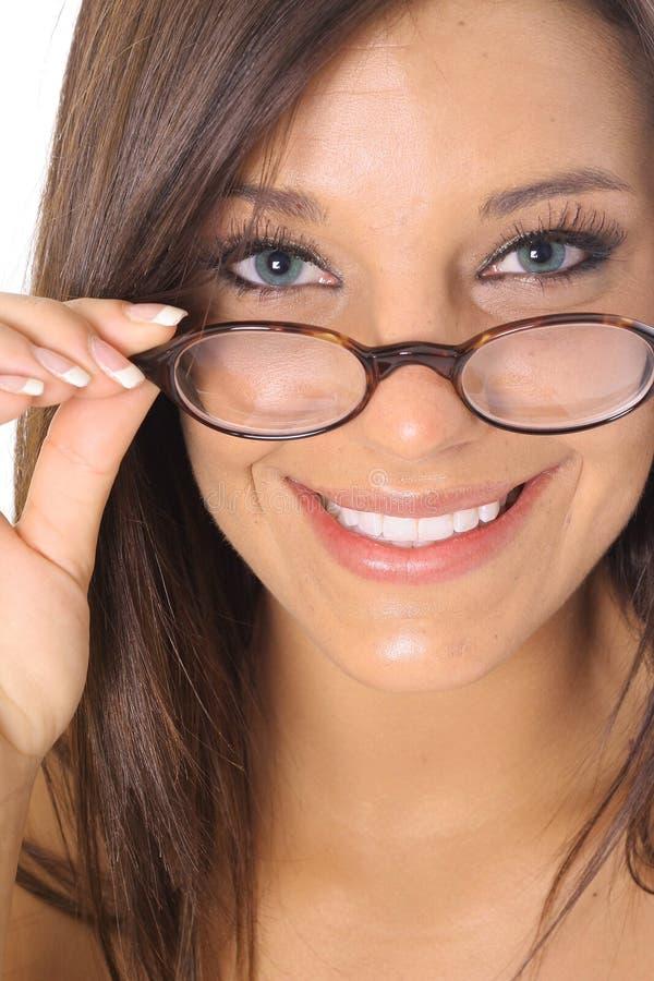 Mujer que tira de los vidrios con una sonrisa magnífica imagen de archivo