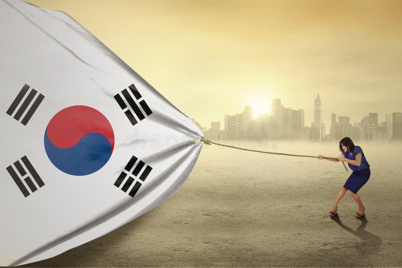Mujer que tira de una bandera surcoreana imagen de archivo
