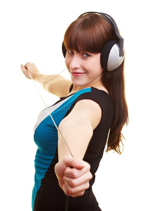 Mujer que tira del cable del auricular imagenes de archivo