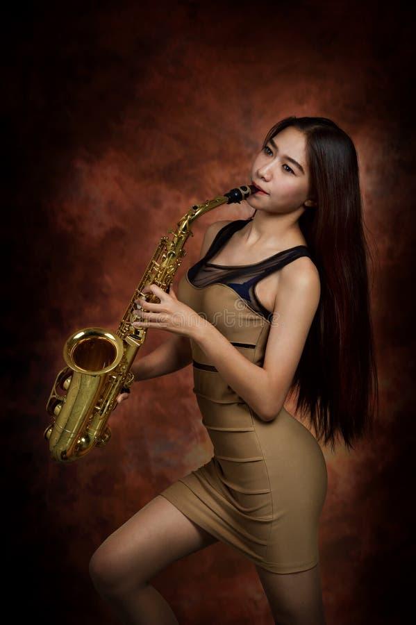 Mujer que toca el saxofón imagen de archivo libre de regalías