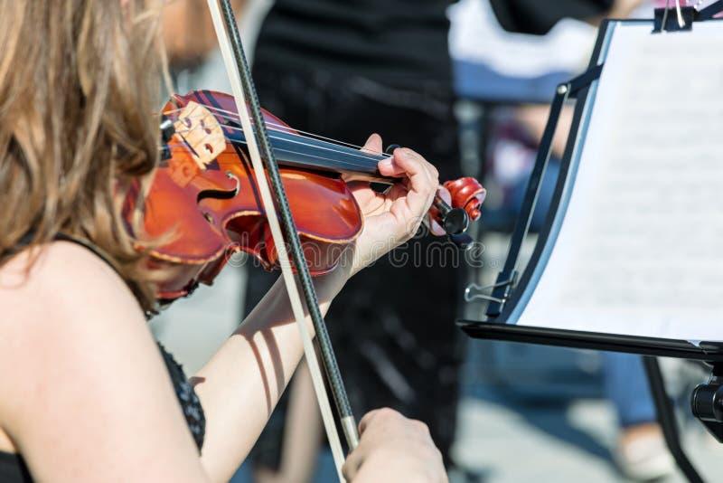 Mujer que toca el violín durante concierto de la música clásica fotografía de archivo