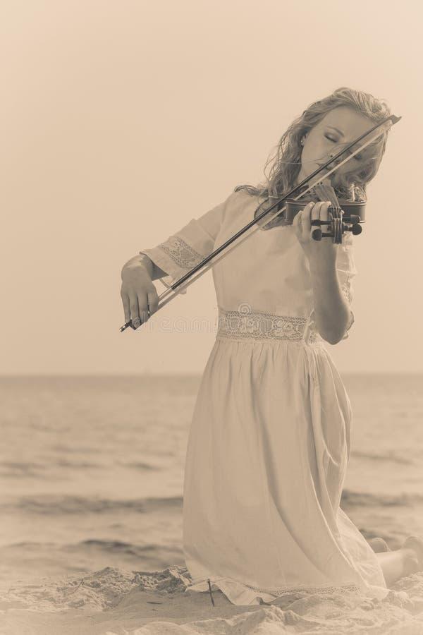Mujer que toca el violín en el violín cerca de la playa foto de archivo