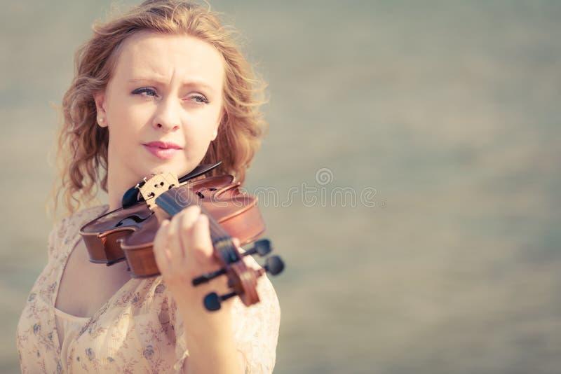 Mujer que toca el violín en el violín cerca de la playa fotos de archivo libres de regalías