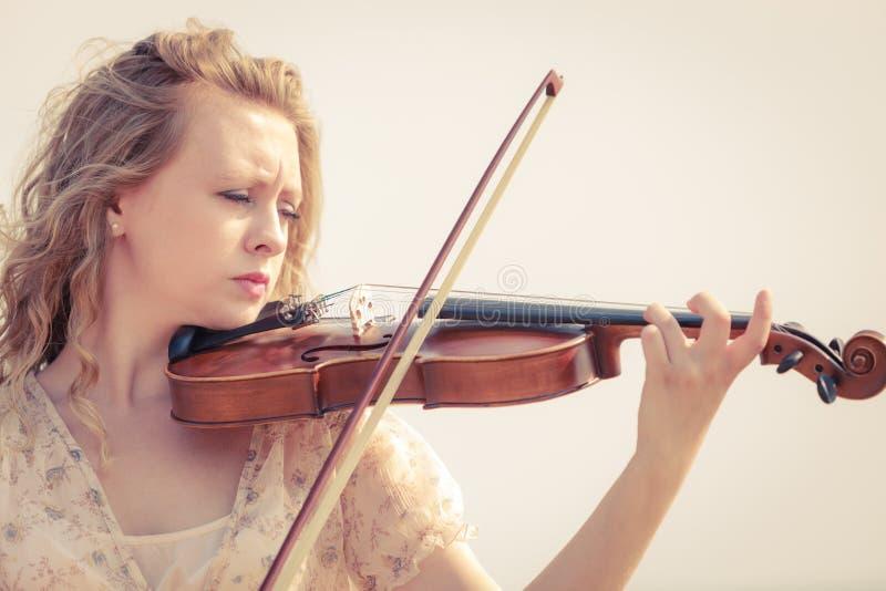 Mujer que toca el violín en el violín cerca de la playa imagen de archivo libre de regalías