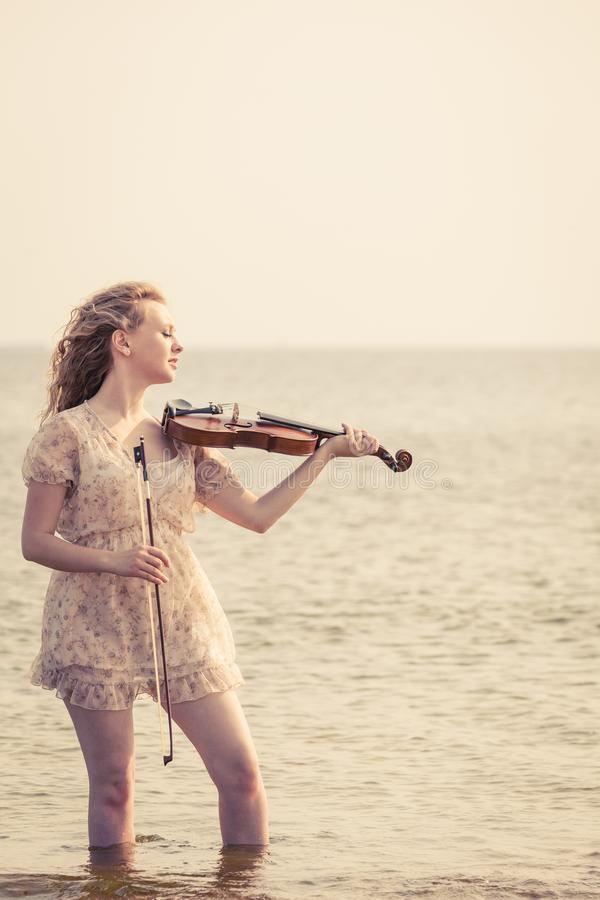 Mujer que toca el violín en el violín cerca de la playa imágenes de archivo libres de regalías