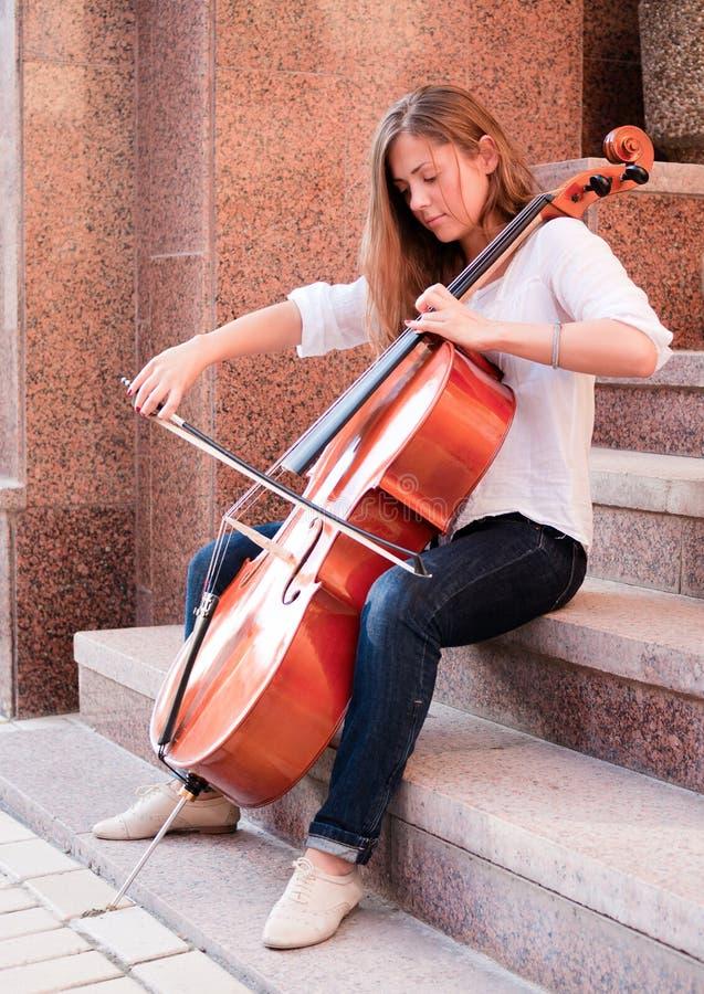 Mujer que toca el violoncelo en la escalera imagen de archivo