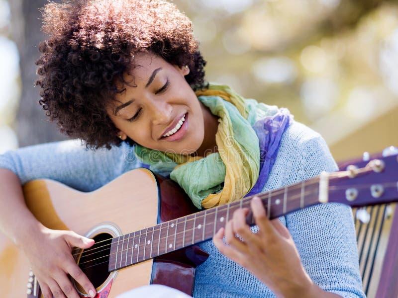 Mujer que toca la guitarra en parque imagen de archivo