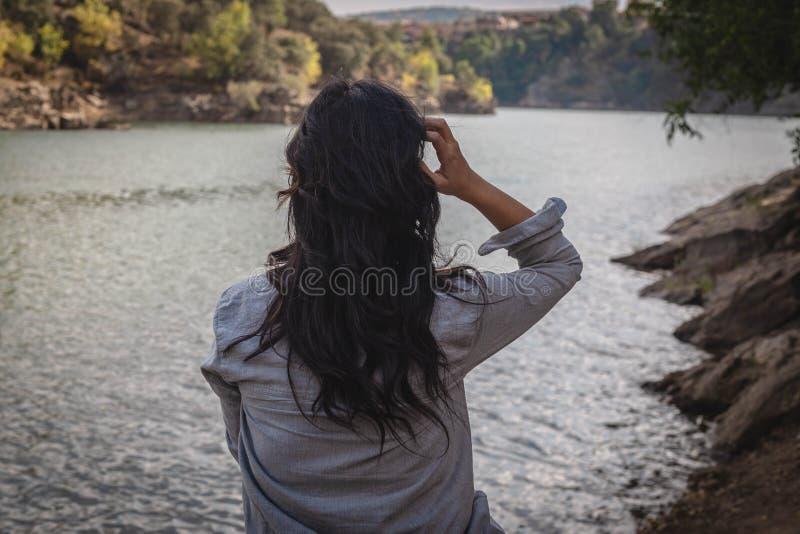 Mujer que toca su pelo en el río que mira el paisaje, Buitrafo de Lozoya, España imagenes de archivo