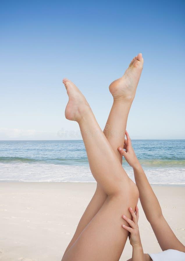 Mujer que toca sus piernas en la playa imágenes de archivo libres de regalías