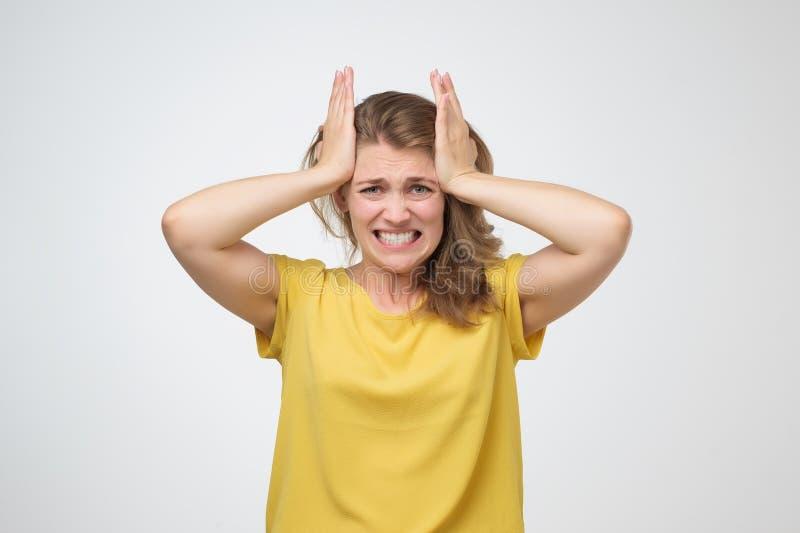 Mujer que toca sus templos que sienten la tensión o el dolor de cabeza terrible imagen de archivo