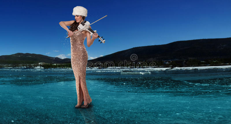 Mujer que toca un violín en un lago congelado fotos de archivo