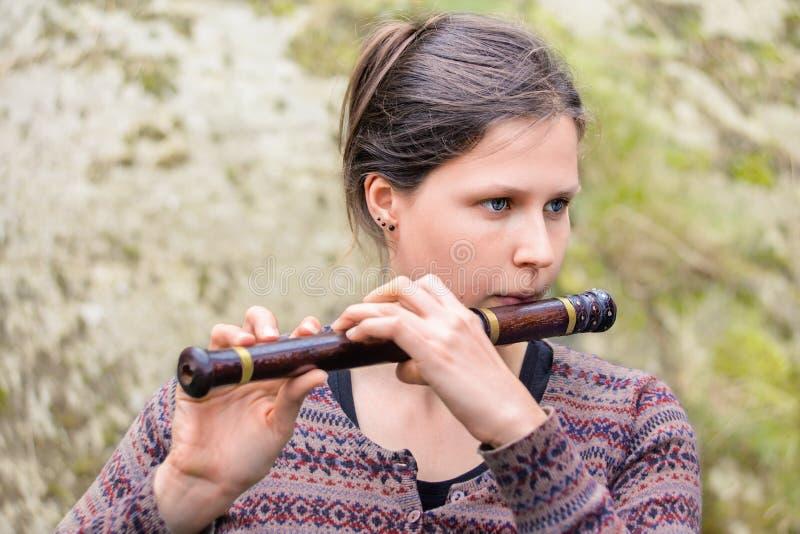 Mujer que toca una flauta de madera india fotos de archivo libres de regalías