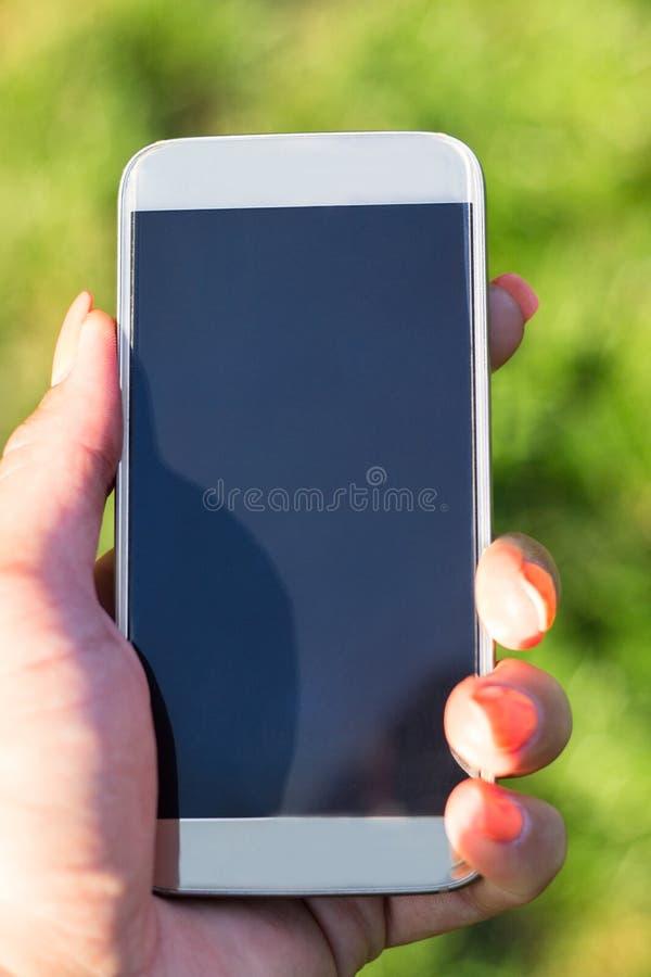 Mujer que toca una pantalla de su smarthone fotos de archivo