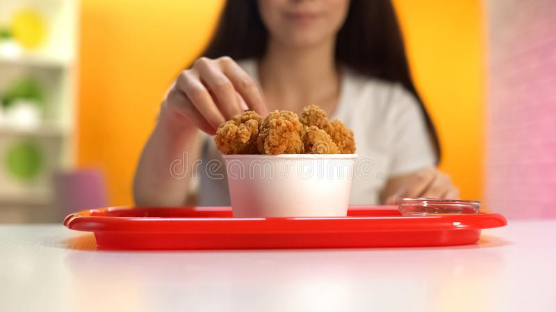 Mujer que toma comida deliciosa pero malsana de las alas de pollo frito, riesgo de la gastritis imagenes de archivo