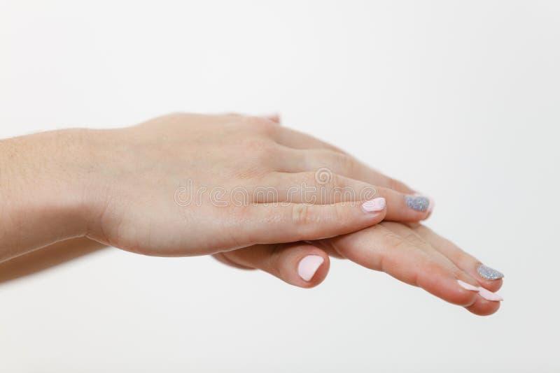 Mujer que toma el cuidado de sus manos secas que aplican la crema fotografía de archivo libre de regalías