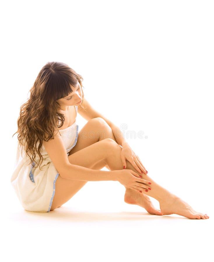 Mujer que toma el cuidado de sus piernas foto de archivo