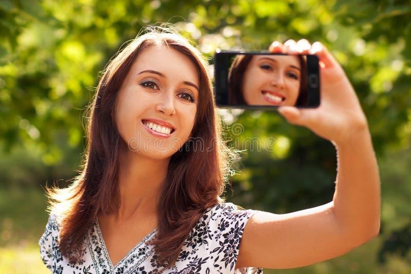 Mujer que toma el retrato de uno mismo con la cámara del teléfono imagen de archivo libre de regalías