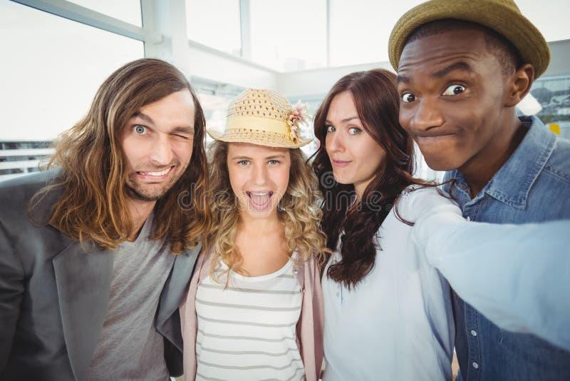Mujer que toma el selfie con los compañeros de trabajo que hacen caras fotografía de archivo libre de regalías