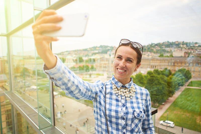 Mujer que toma el selfie contra paisaje urbano imagen de archivo libre de regalías