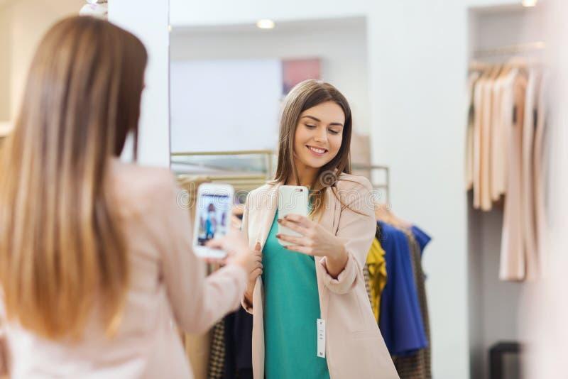 Mujer que toma el selfie del espejo por smartphone en la tienda foto de archivo libre de regalías