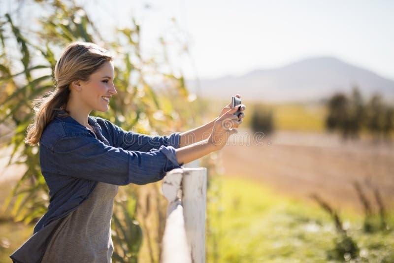Mujer que toma el selfie en el teléfono móvil en parque imagenes de archivo
