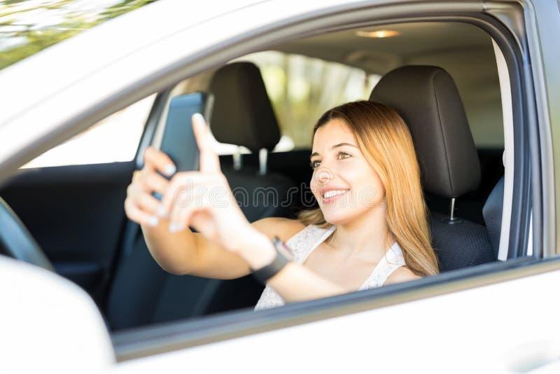 Mujer que toma el selfie en su nuevo coche foto de archivo
