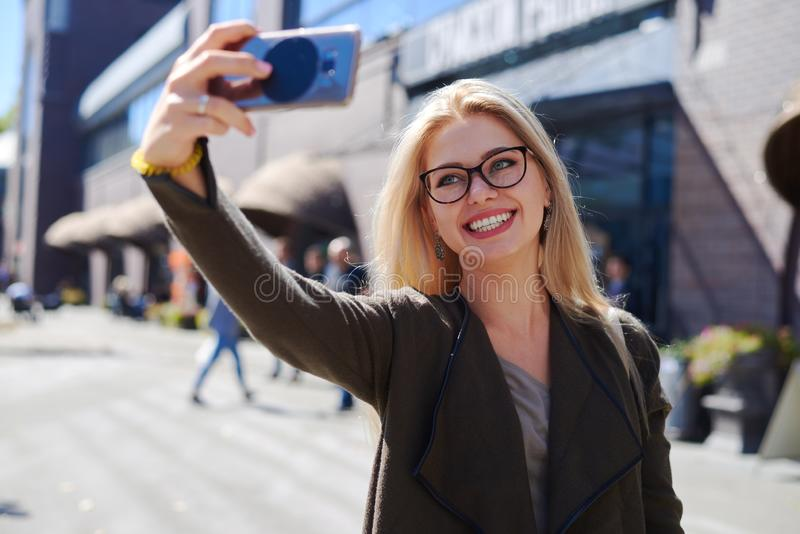 Mujer que toma el selfie usando cámara móvil en ciudad imágenes de archivo libres de regalías