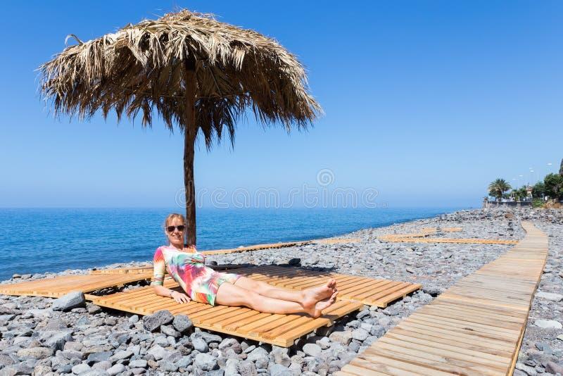 Mujer que toma el sol como turista en la playa portuguesa pedregosa imagen de archivo libre de regalías
