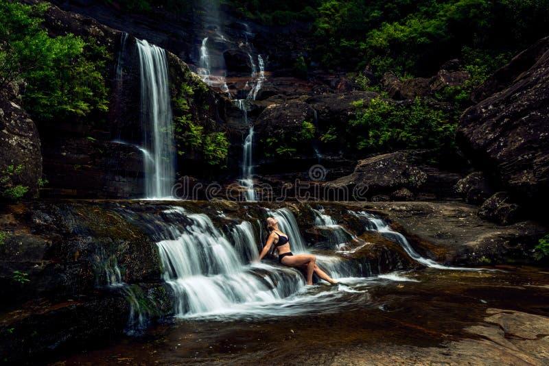 Mujer que toma el sol en cascada enorme de la montaña imágenes de archivo libres de regalías