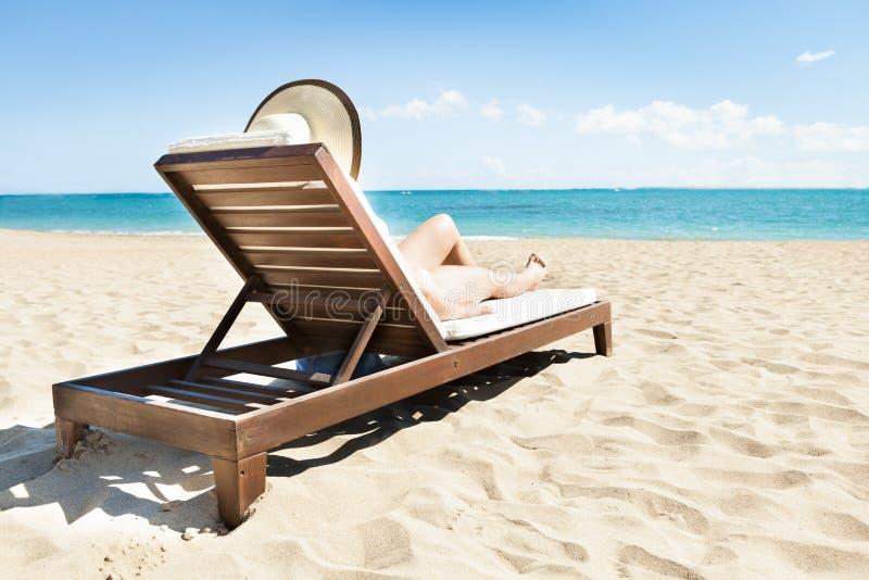Mujer que toma el sol en silla de cubierta en la playa fotos de archivo libres de regalías
