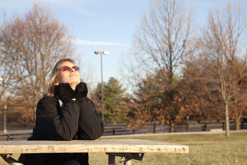 Mujer que toma el sol en sol del invierno fotos de archivo libres de regalías