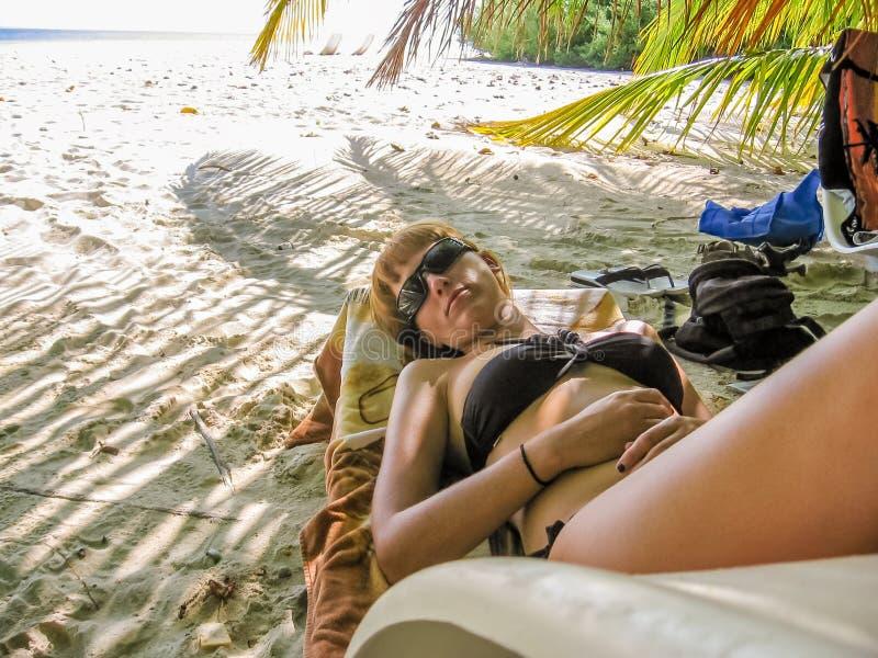 Mujer que toma el sol en vacaciones de verano foto de archivo